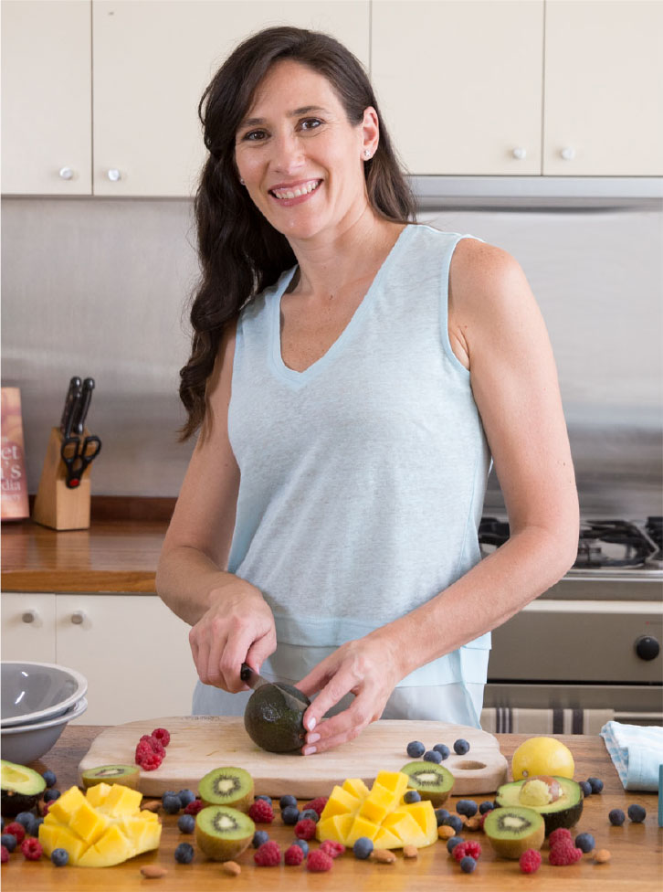 Melanie McGrice in the kitchen chopping fruit