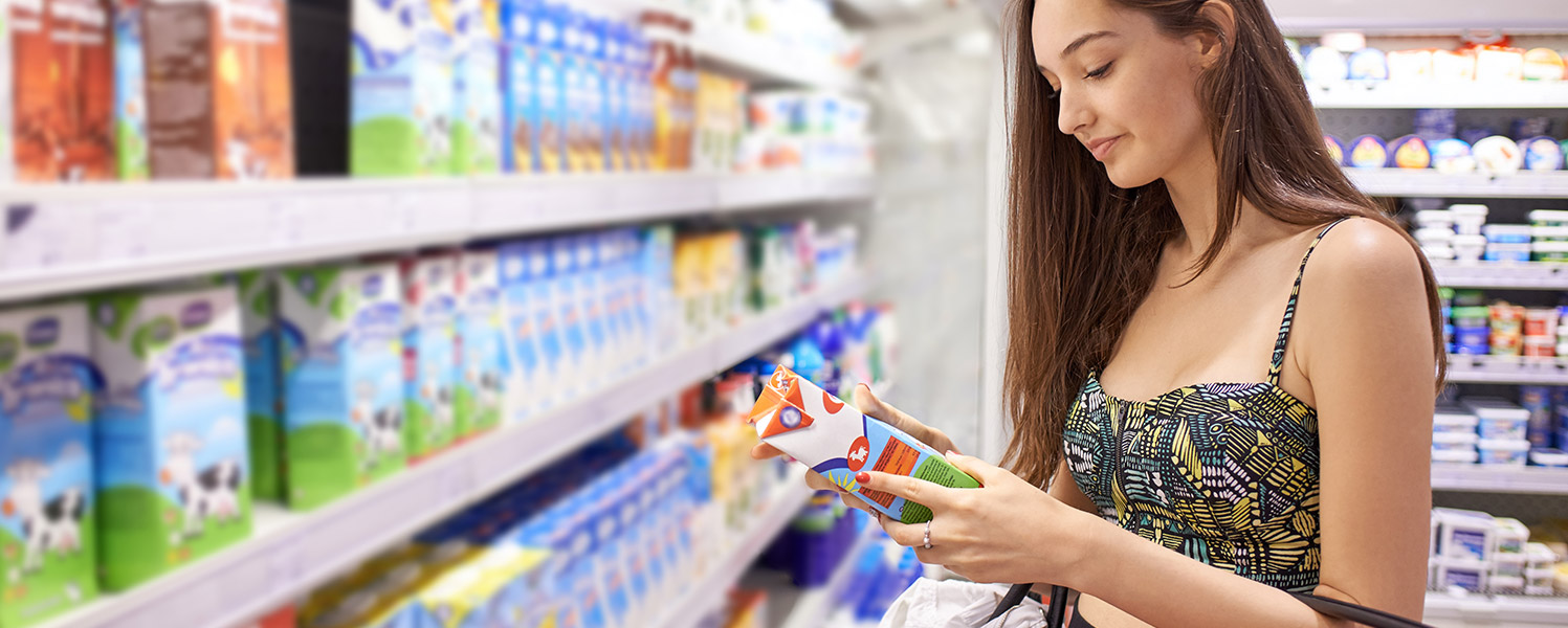 Woman in supermarket reading a product label